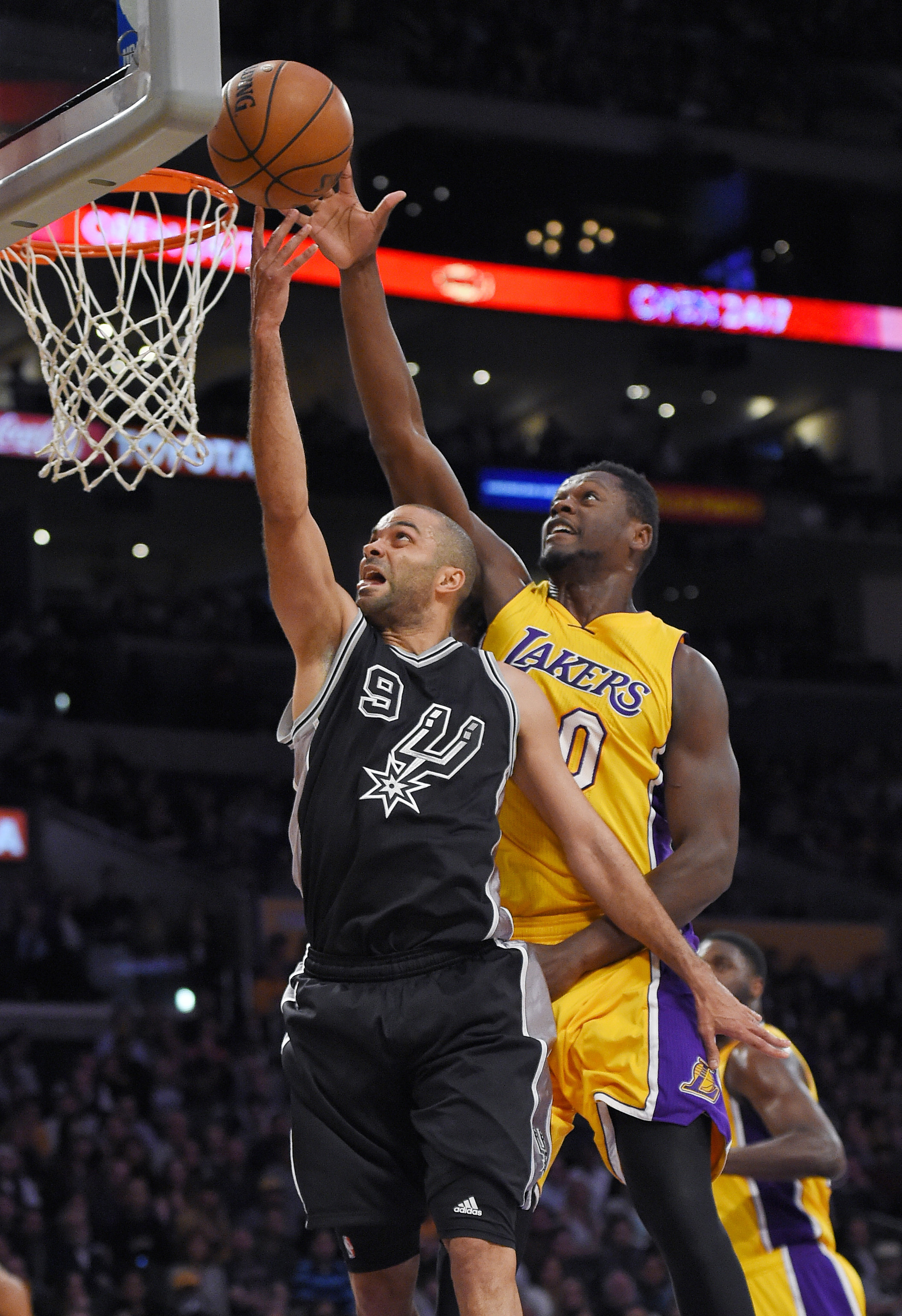 San Antonio Spurs guard Tony Parker, left, shoots as Los Angeles Lakers forward Julius Randle defends during the first half of an NBA basketball game Friday, Jan. 22, 2016, in Los Angeles. (AP Photo/Mark J. Terrill)