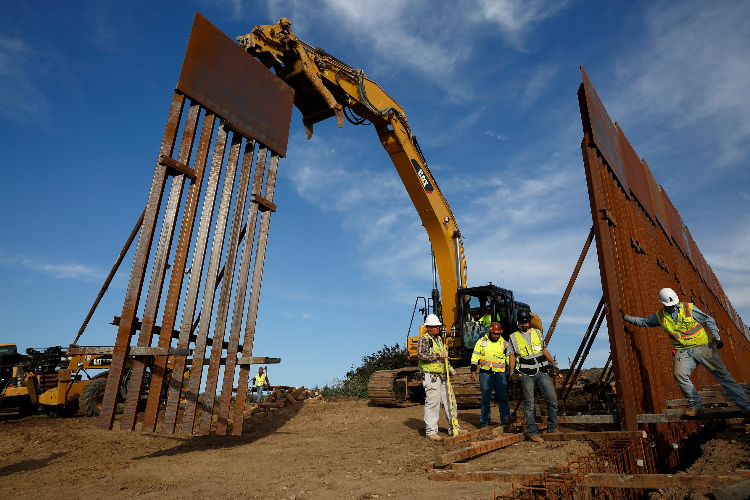 FILE - In this Jan. 9, 2019 file photo, construction crews install new border wall sections seen from Tijuana, Mexico. (AP Photo/Gregory Bull, File)