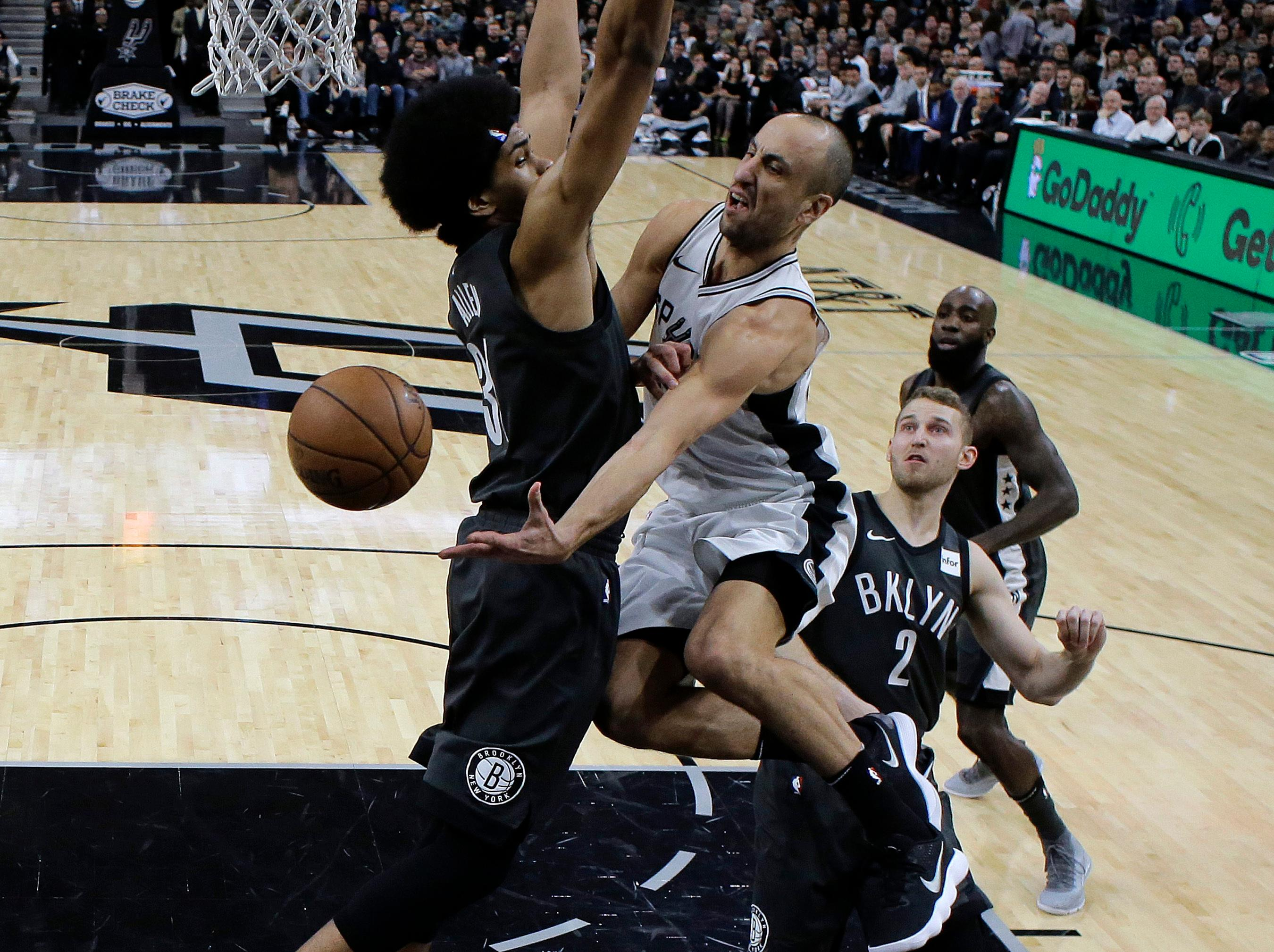 San Antonio Spurs guard Manu Ginobili, center, drives to the basket past Brooklyn Nets center Jarrett Allen, left, during the first half of an NBA basketball game, Tuesday, Dec. 26, 2017, in San Antonio. (AP Photo/Eric Gay)