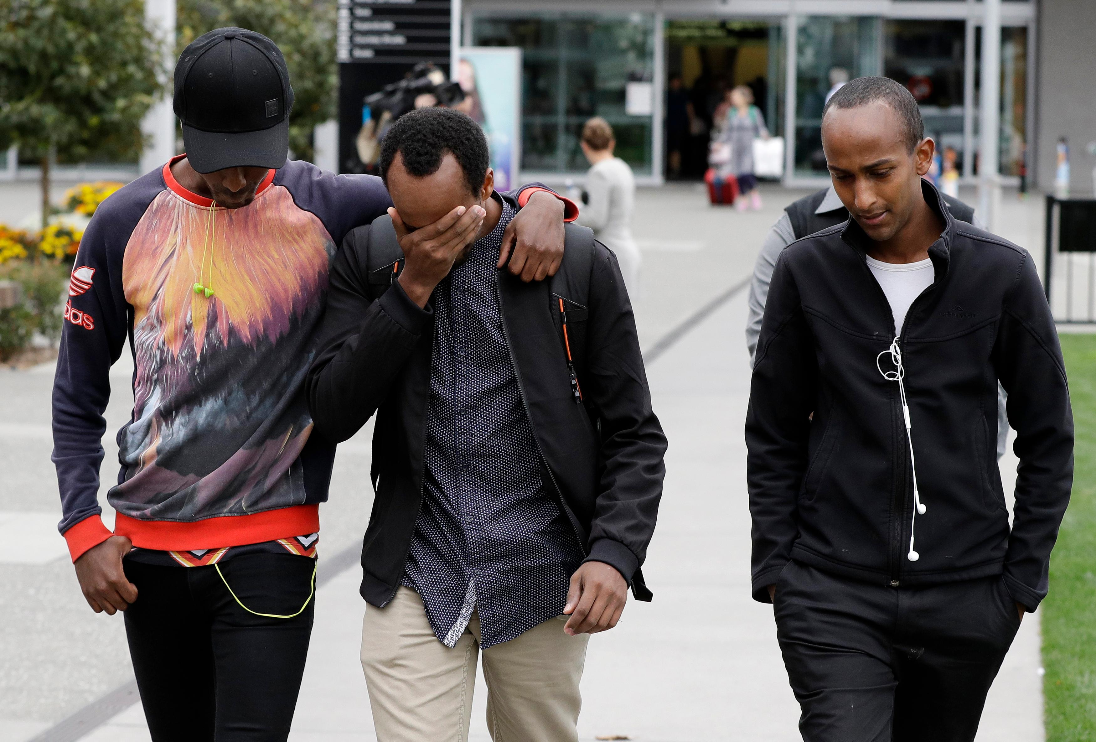 Abdifatah Ibrahim, center, and his brother Abdi, right, walk with an unidentified friend in Christchurch, New Zealand, Sunday, March 17, 2019. (AP Photo/Mark Baker)