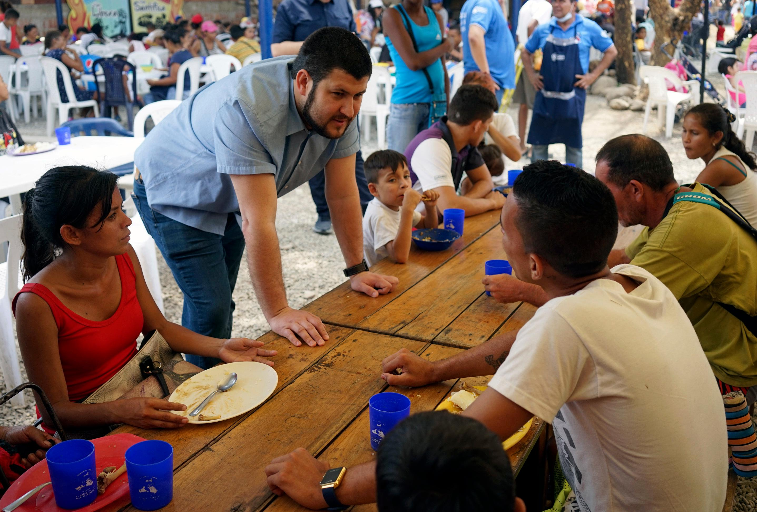 "Opposition leader David Smolansky talks with Venezuelans eating at the ""Divina Providencia"" soup kitchen for migrants in Cucuta, Colombia, Thursday, Feb. 21, 2019.{ } (AP Photo/Christine Armario)"