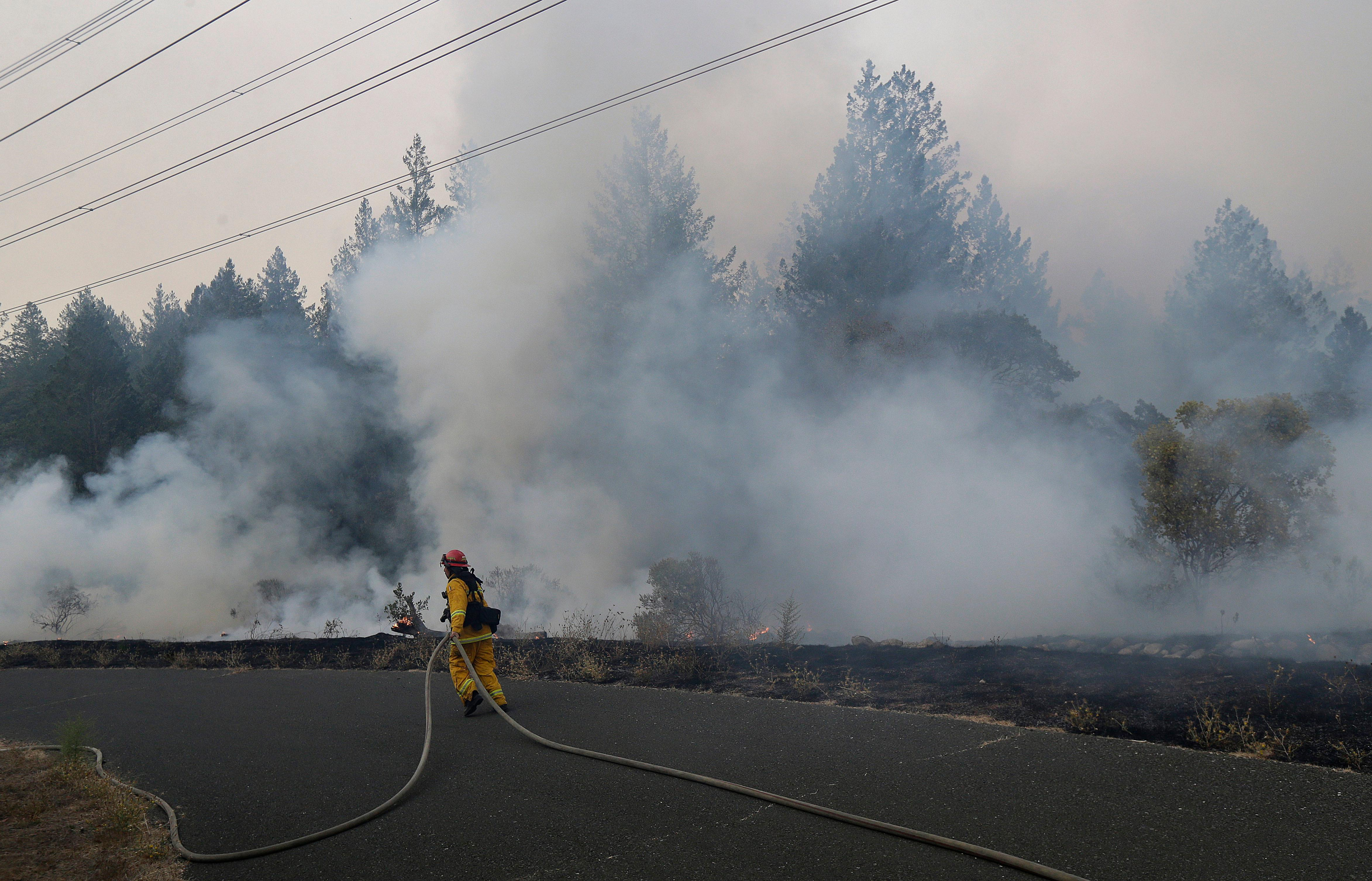 Santa Rosa firefighters work on a fire on the side of a road near the Oakmont area in Santa Rosa, Calif., Tuesday, Oct. 10, 2017. (AP Photo/Jeff Chiu)