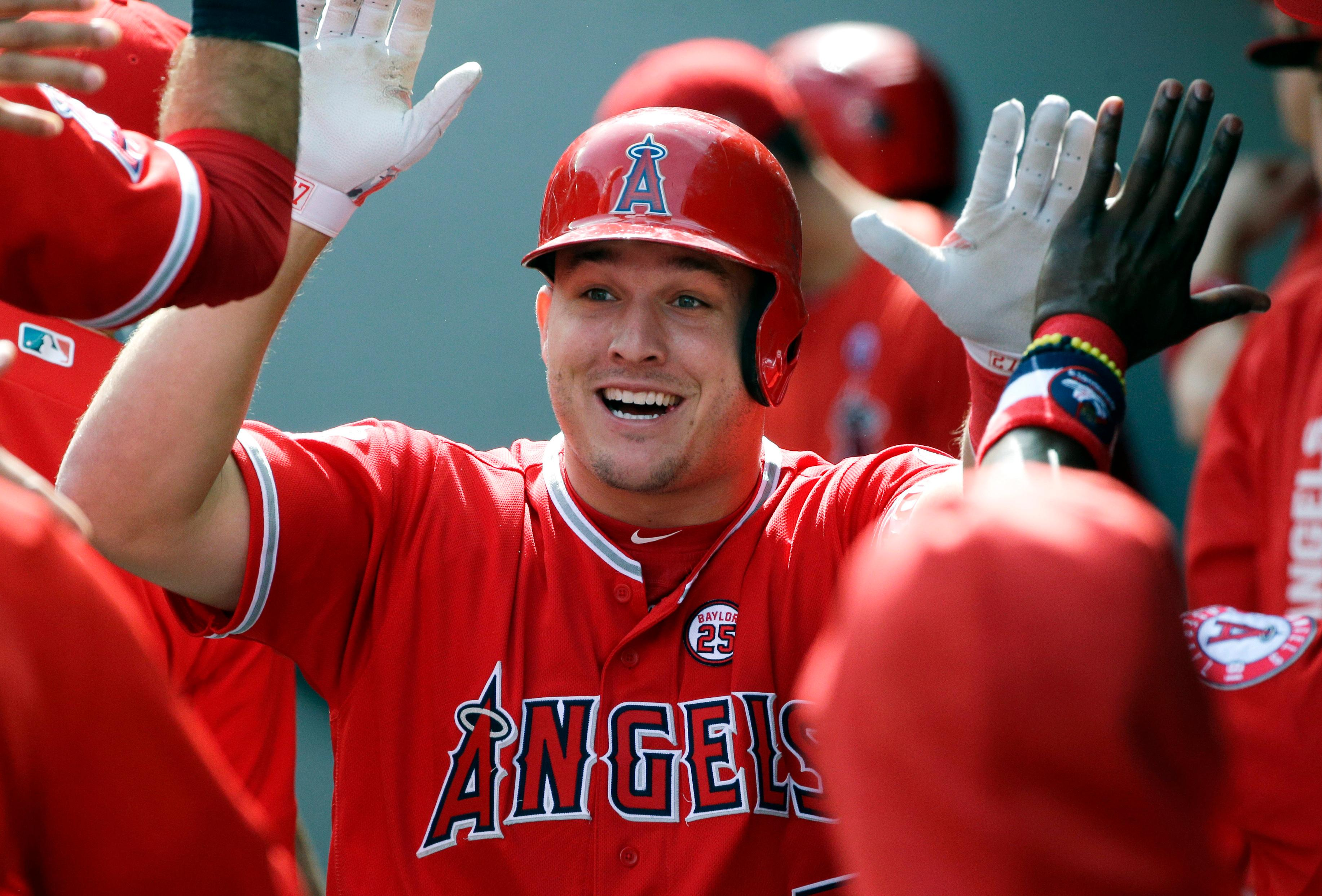 FILE - In this Sept. 10, 2017, file photo, Los Angeles Angels' Mike Trout is greeted in the dugout after hitting a solo home run in the first inning of a baseball game against the Seattle Mariners in Seattle. A person familiar with the negotiations tells The Associated Press Tuesday, March 19, 2019, that Trout and the Angels are close to finalizing a record $432 million, 12-year contract that would shatter the record for the largest deal in North American sports history.  (AP Photo/Ted S. Warren, File)