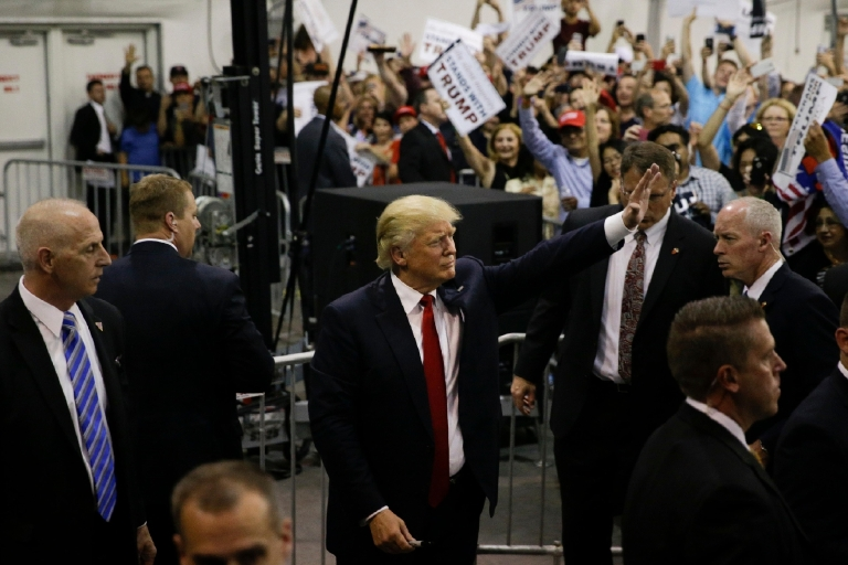 Republican presidential candidate Donald Trump waves to the crowd as he is surrounded by Secret Service agents after a rally, Thursday, June 2, 2016, in San Jose, Calif. (AP Photo/Jae C. Hong)