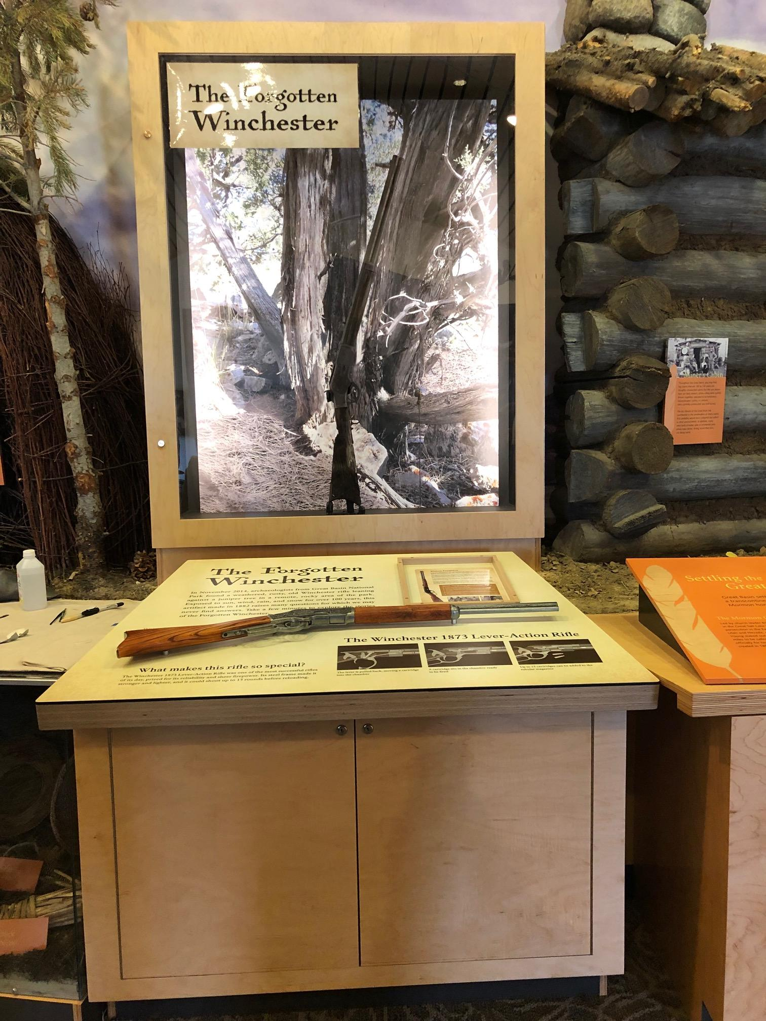 "<p>Image of the ""Forgotten Winchester"" in the new exhibit. The background features an image of the tree it was found leaning against so visitors can imagine what it would have been like to discover the rifle themselves. (Photos courtesy of National Park Service)</p>"