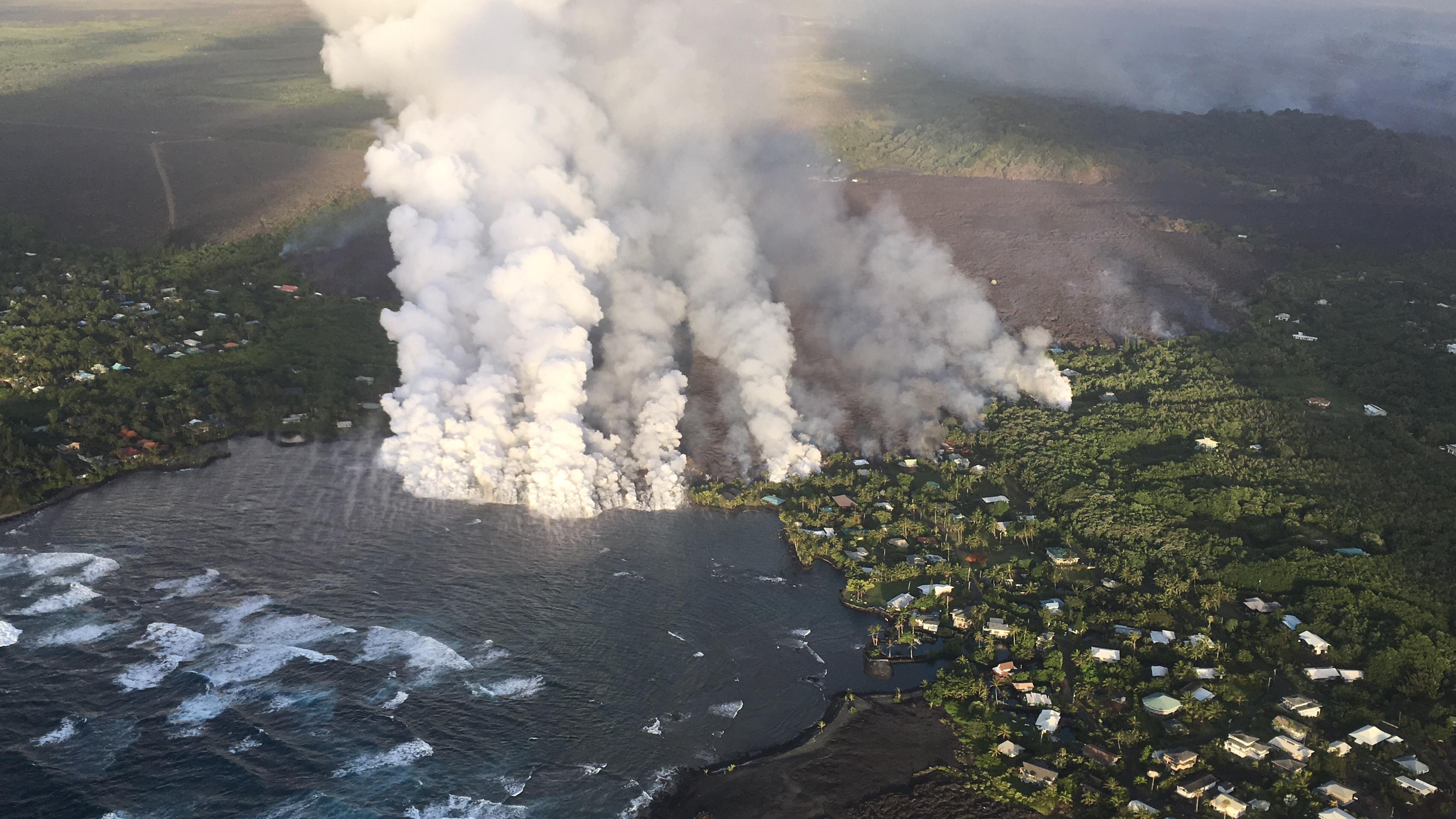 Overflight photograph at approximately 6:13 a.m. HST shows the lava flow originating from Fissure 8 (not visible in photograph) entering Kapoho Bay. The ocean entry was reported to have occurred by 10:30 p.m. on the night of June 3, 2018. (USGS)